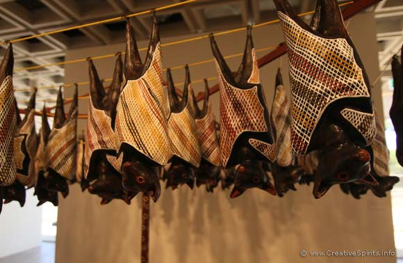 Detail showing the carved wooden fruit bats hanging from a clothes line.