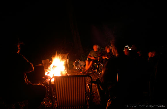 A group of Aboriginal people sits around a campfire.