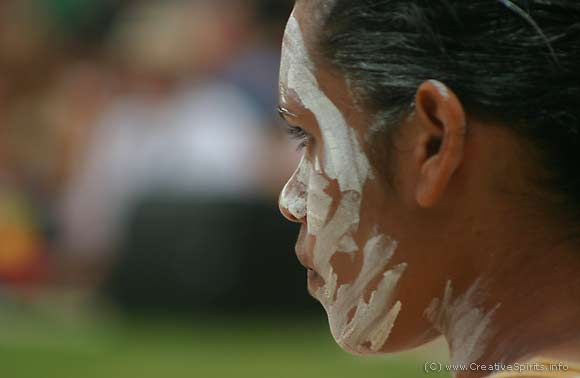 An Aboriginal woman with ochre marks in her face looking into the distance.