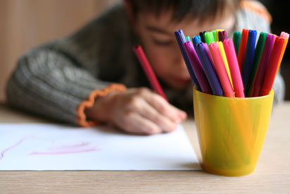 Child drawing a picture, pens in foreground.