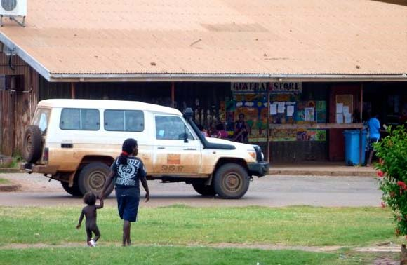 Two people walk in front of the General Store where a 4WD is parked.