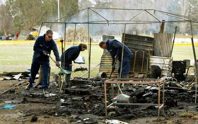 Police officers rummaging in the smouldering remains of the tent embassy.