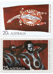 Two stamps showing the bark painting of a turtle and two men wearing body decoration.