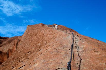 Tourists climbing Uluru