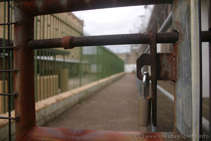 Circle sentencing: A lock bars the way into an outside corridor with fences to either side.