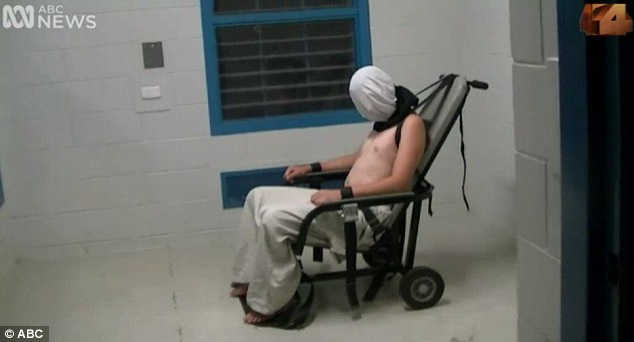 A bare-chested teenager sits bound and hooded in a chair.