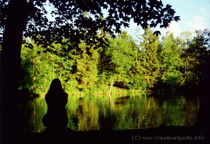 The dark outline of a woman sitting by herself at the shore of a lake.