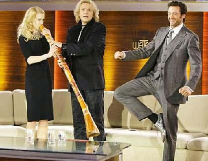 Actress Nicole Kidman blows the didgeridoo while actor Hugh Jackman imitates an Aboriginal man standing on one leg.