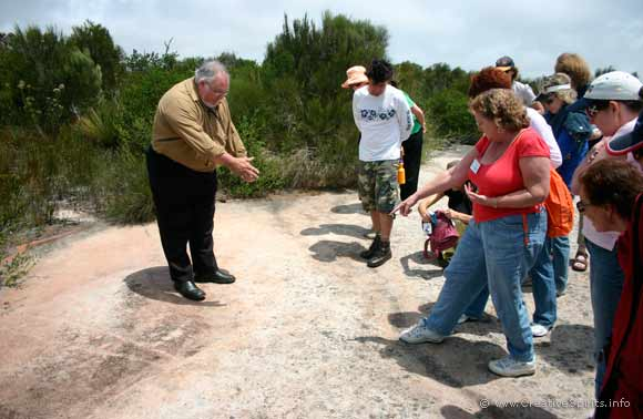 Les Bursill pointing to a rock engraving with tour participants looking on.