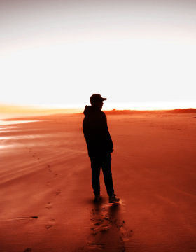 The black silhouette of a man walking on a red sandy beach.