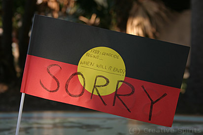 An Aboriginal flag with the words '1788: Genocide begins...when will it end? Sorry.'.