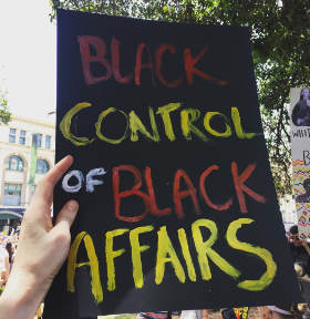 A poster reading 'Black control of black affairs'.