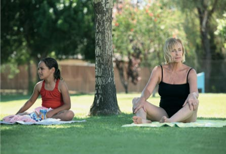 Still image from 'Mixed Bag' showing the woman sitting in the grass with an Aboriginal girl next to her.