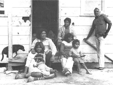 Essie's family gather in front of a simple wooden house entry.
