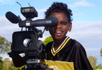 A young Indigenous boy behind a professional camera.