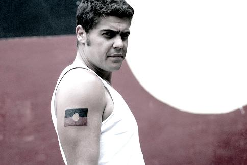 Dan Sultan portrait in front of an Aboriginal flag.